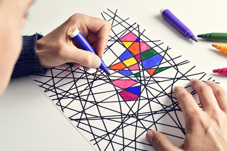 fineliner: closeup of a young man coloring an abstract drawing. Stock Photo