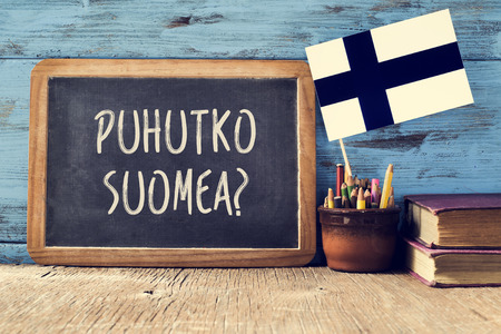 finnish: a chalkboard with the question puhutko suomea, do you speak Finnish written in Finnish.