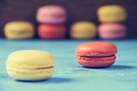 lomography: some appetizing macarons with different colors and flavors on a blue rustic wooden surface Stock Photo