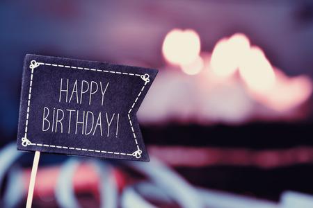 gros plan d'un panneau en forme de drapeau noir avec le texte joyeux anniversaire, et un gâteau d'anniversaire avec des bougies allumées en arrière-plan