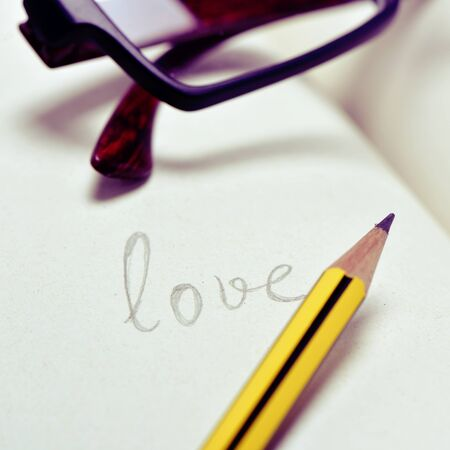 teenagers learning: closeup of a pair of eyeglasses and the word love handwritten in a notebook with a pencil