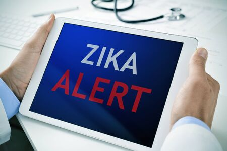 albopictus: closeup of a doctor man sitting at his office desk holding a tablet computer with the text zika alert in its screen