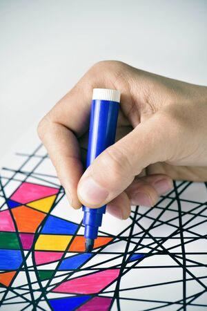 pens: closeup of a young man coloring an abstract drawing, designed by myself, with marker pens of different colors Stock Photo