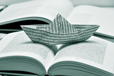 prose: closeup of a paper boat, made with a printed paper with non-sense words, on an open book, in black and white