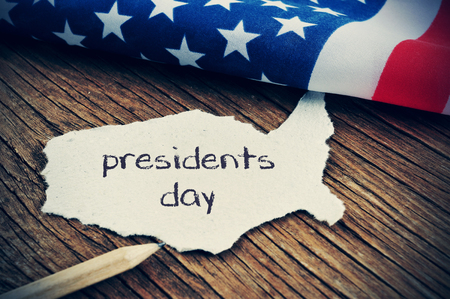 a piece of paper in the shape of the United States with the word presidents day written in it, placed on a wooden background next to the flag of the United States, with a slight vignette added