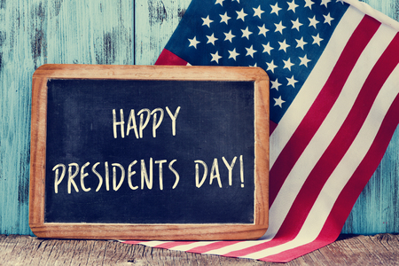 the text happy presidents day written in a chalkboard and a flag of the United States, on a rustic wooden background