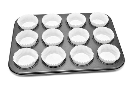 baking tray: a baking tray with different holes for muffins or cupcakes, with some paper cups, on a white background