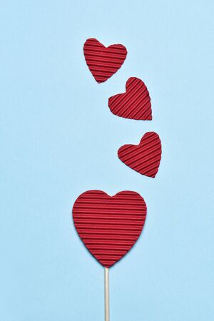 paperboard: some hearts made with red corrugated paperboard, one of them stacked in a stick like a lollipop, against a blue background