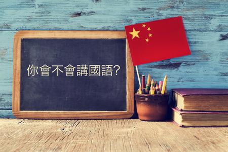 una lavagna con la domanda parli cinese? scritto in cinese, una pentola con le matite, alcuni libri e la bandiera della Cina, su una scrivania di legno