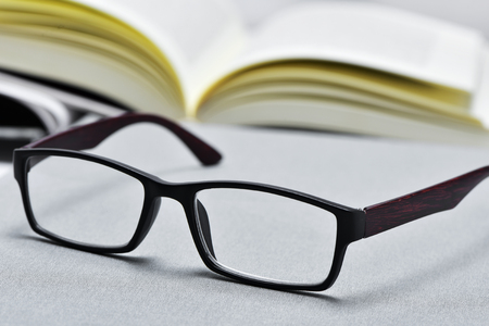 prose: closeup of a pair of eyeglasses and an open book in the background