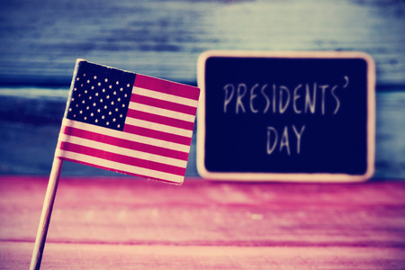 president's day: the flag of the United States and the text the text presidents day written in a chalkboard, placed on a blue and red rustic wooden background Stock Photo