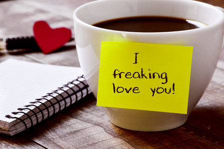 closeup of a yellow sticky note with the text I freaking love you attached to a cup of coffee, on a rustic wooden table, next to a notebook, a red heart and a pen
