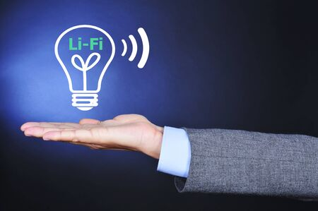 fidelity: closeup of a man wearing a suit with an illustration of a lightbulb and the text Li-Fi, Light Fidelity, in the palm of his hand Stock Photo