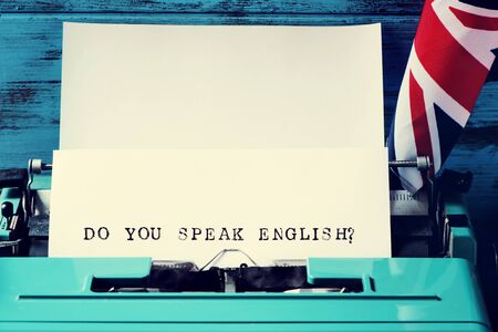 schoolroom: closeup of a paper in an old blue typewriter with the question do you speak english? typewritten in it, and the flag of the United Kingdom