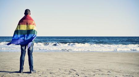 後ろから見た若い白人男に包まれた海を見て虹色の旗
