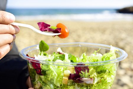 closeup of a young caucasian man eating a prepared salad next to the sea Stock Photo