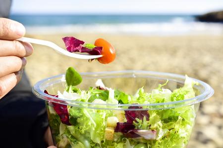 closeup of a young caucasian man eating a prepared salad next to the sea Standard-Bild