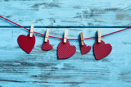 clothespegs: some hearts, made with red corrugated paperboard, hung with clothespins in a clothes line, against a blue rustic wooden background