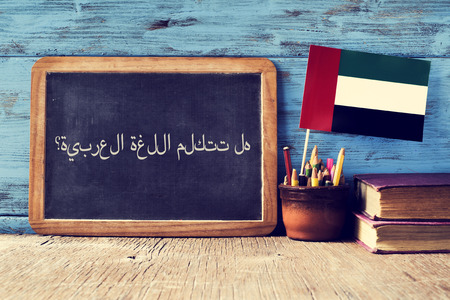 learning arabic: a chalkboard with the question do you speak Arabic? written in Arabic, a pot with pencils, some books and the flag of the United Arab Emirates, on a wooden desk