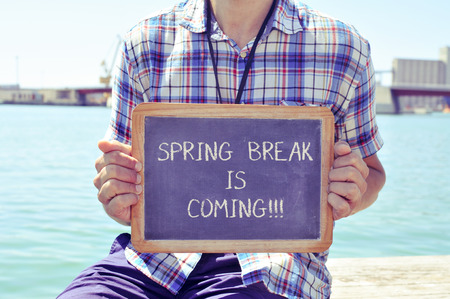 spring break: a young caucasian man sitting in a wooden pier shows a chalkboard with the text spring break is coming written in it, with a filter effect