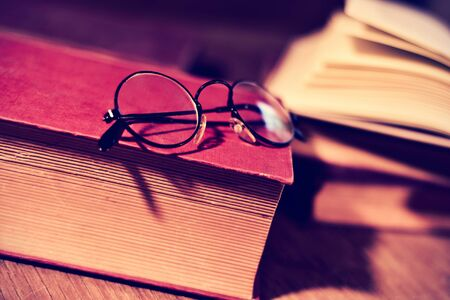 bibliophile: closeup of a pair of retro round-framed eyeglasses and some old book on a rustic wooden table. Stock Photo