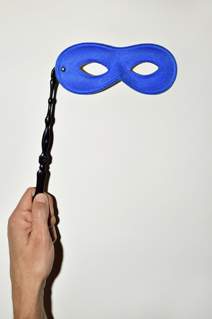 handled: closeup of the hand of a young caucasian man holding a handled blue carnival mask against a white background, with a hard shadow simulating a snapshot
