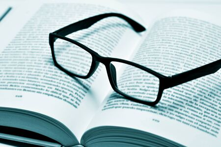 erudition: closeup of a pair of black plastic-rimmed eyeglasses on an open book, in duotone
