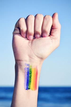 rainbow flag: closeup of a young caucasian man with his fist raised to the sky and a rainbow flag painted in his wrist, with the ocean in the background