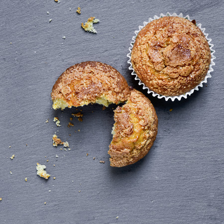 muffin: high-angle shot of some plain muffins on a slate background