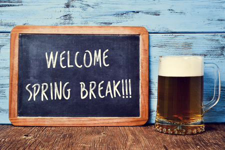 an old chalkboard with the text welcome spring break written in it and a jar with refreshing beer on a rustic wooden table