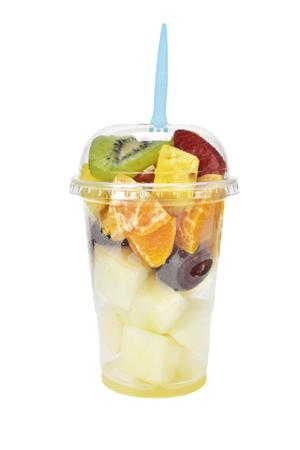 ensalada de frutas: una ensalada de frutas en un vaso de plástico desechable, sobre un fondo blanco Foto de archivo