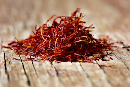 a pile of saffron threads on a rustic wooden table Stockfoto
