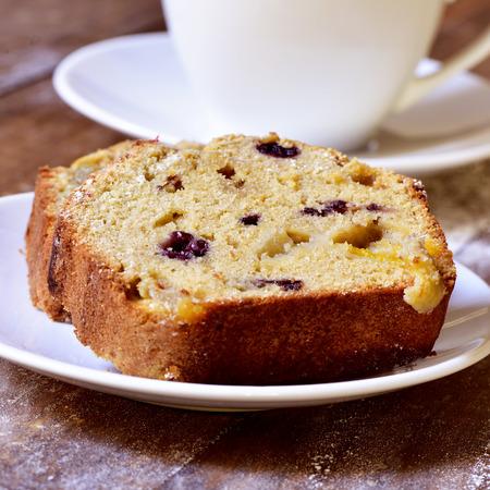 postres: primer plano de un trozo de pastel de frutas en un plato blanco y una taza de café o té en una mesa de madera rústica Foto de archivo