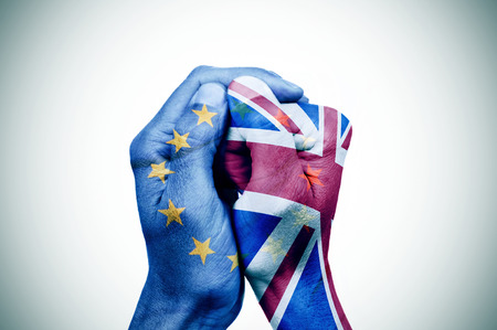 politics: hand patterned with the flag of the European Community envelops another hand patterned with the flag of the United Kingdom