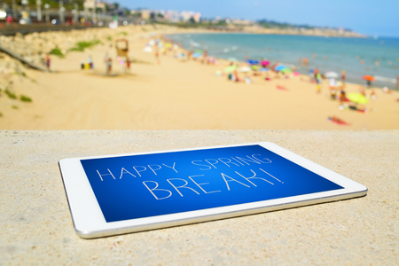 spring break: closeup of a tablet computer with the text happy spring break and the beach with many sunbathers in the background