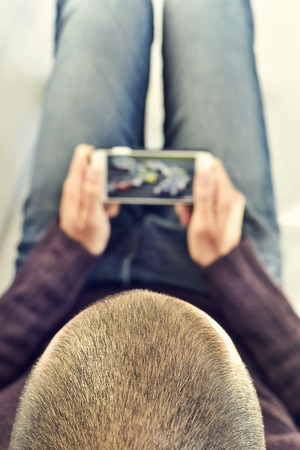 broadcast: a young man lying on the couch watches a car race in streaming in his smartphone