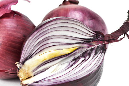 red onions: closeup of some raw red onions on a white background