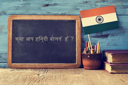 una lavagna con la domanda ti parla hindi? scritto in Hindi, una pentola con matite, alcuni libri e la bandiera dell'India, su una scrivania in legno
