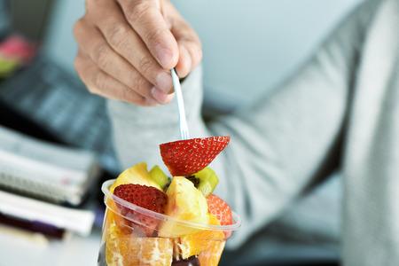 ensalada de frutas: Primer plano de un hombre caucásico joven comer una ensalada de frutas en un vaso de plástico transparente en la oficina