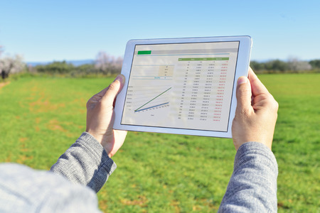 closeup of a young farmer observing some charts in a tablet computer in a fallow field Banco de Imagens - 52797980