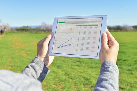 primer plano de un joven agricultor observar algunos gráficos en un equipo Tablet PC en un campo en barbecho