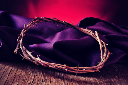 catholicism: closeup of the the crown of thorns of Jesus Christ on a purple fabric