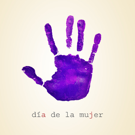 egalitarianism: a violet handprint and the text dia de la mujer, womens day in spanish, on a beige background