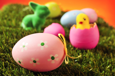 huevos de pascua: closeup of a pink decorated egg on the grass with some other colorful decorated eggs, a green easter rabbit and a toy chick emerging from a pink egg in the background Foto de archivo
