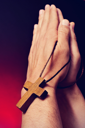 crucify: closeup of a young caucasian man praying with a wooden cross in his hands