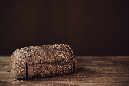 a sliced loaf of rye bread topped with sunflower seeds on a rustic wooden surface, in sepia toning