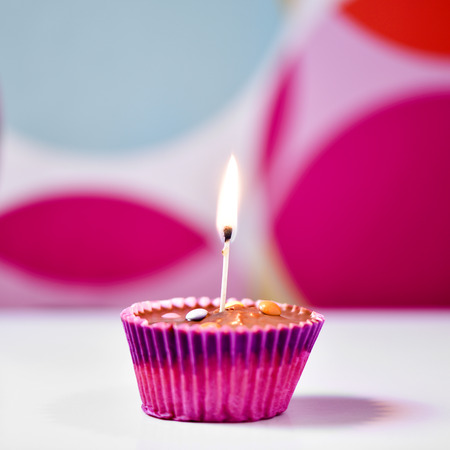 lighted: a chocolate cupcake topped with a lighted match on a white surface against a colorful geometric-patterned background Stock Photo