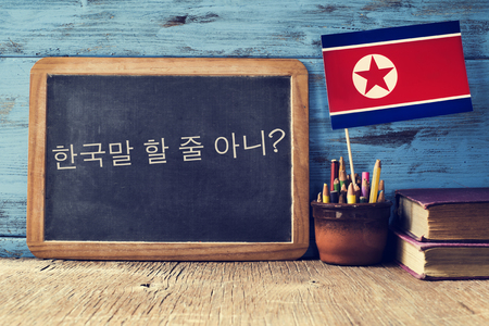 languages: una pizarra con la pregunta ¿te habla coreano? escrito en coreano, un bote con lápices, algunos libros y la bandera de Corea del Norte, en un escritorio de madera Foto de archivo
