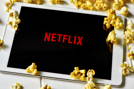 Barcelona, Spain - February 24, 2016: Popcorn and a tablet computer with the Netflix homepage in its screen. The provider of streaming movies and TV series was launched in Spain on October 2015