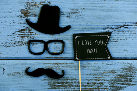 """一个黑色的旗帜形状的招牌,上面写着""""爸爸我爱你"""",一撇小胡子,一副眼镜和一顶帽子,在一个蓝色的粗糙的木头表面上形成了一个男人的脸"""